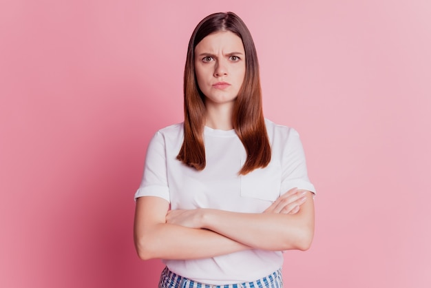 Beautiful upset girl frowning offended face isolated over pink background