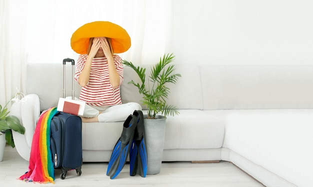 Beautiful upset girl in a yellow hat stays at home and plans a trip on vacation.waiting for travel.
