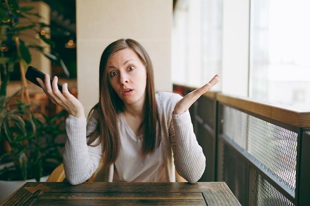 아름다운 화가 여성은 커피숍의 큰 창문 근처에 혼자 앉아 자유 시간에 레스토랑에서 휴식을 취합니다. 휴대 전화로 대화를 나누는 슬픈 여성, 카페에서 휴식. 라이프 스타일 개념입니다.
