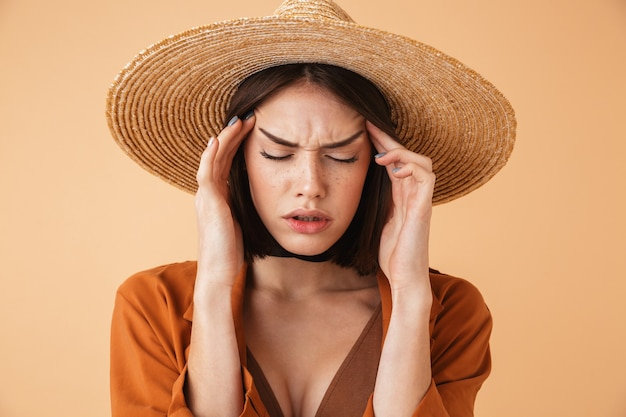 Beautiful upset young woman wearing straw hat standing isolated over beige wall, suffering from a headache