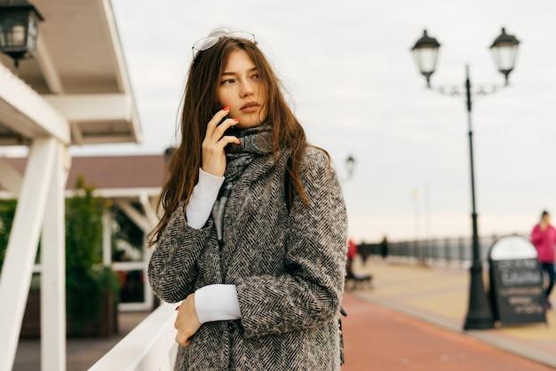 Красивая городская брюнетка девушка в сером пальто гуляет на открытом воздухе, разговаривает по телефону, уличный стиль