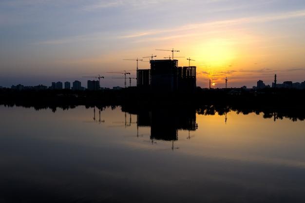 夜明けの美しい都市建設現場のシルエット。湖の水の反射と朝の街並み。