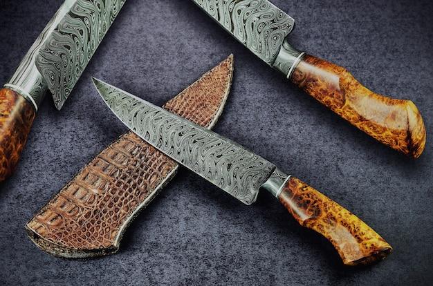 Красивые универсальные ножи в дамасском узоре с ручкой из благородного дерева на темном столе