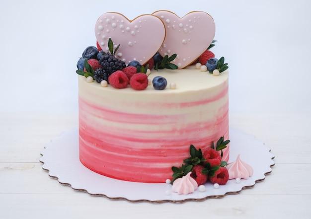Beautiful valentine cake decorated with fresh raspberries, blackberries and blueberries,
