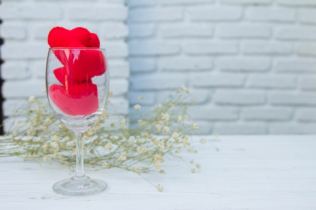 Beautiful valentine red hearts in wine glass decorated with white flowers on brick background