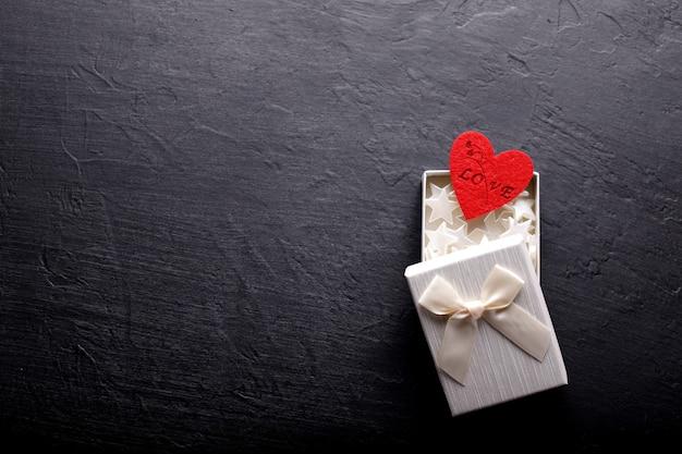黒の背景に赤いハートと美しいバレンタインデーの背景。バレンタインデーのカード。愛の概念。