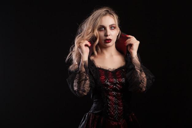 ハロウィーンのための黒いドレスを着た美しい吸血鬼の女性。セクシーな吸血鬼の女性。