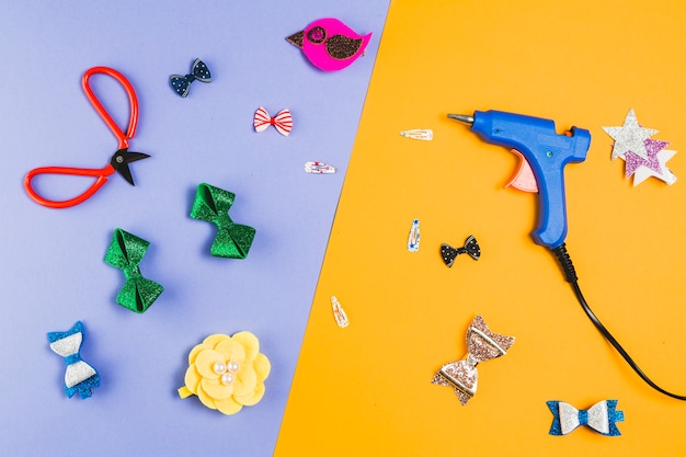 Beautiful various hair clip with scissor and hot glue gun over dual background