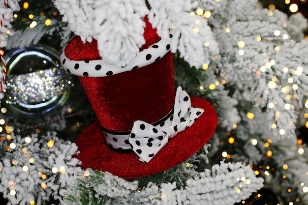 モミの枝に美しいベルベットの帽子クリスマスのおもちゃ雪に覆われた枝
