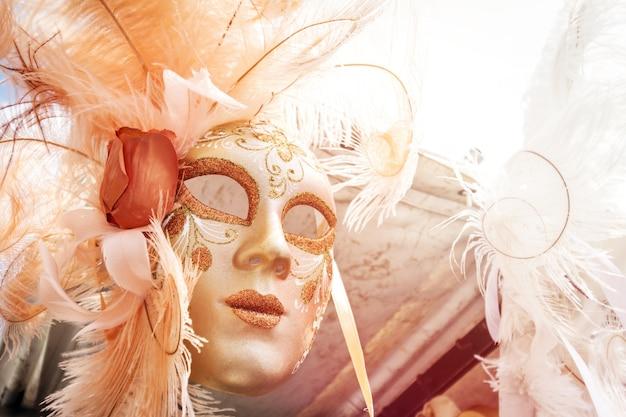 Красивая венецианская маска, висящая на продажу. солнечный свет, дневной свет. тонизирующий. горизонтальный.