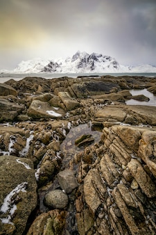 Beautiful vertical image of a rocky atlantic shore with snow covered mountain