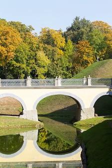 Красивый вертикальный пейзаж с осенним лесом, рекой и старинным мостом.