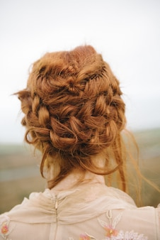 Beautiful vertical picture of braided hair of a ginger female