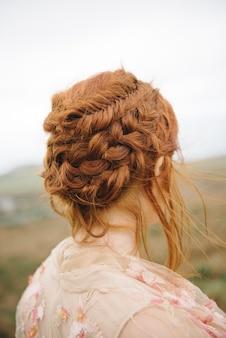 Bella immagine verticale di capelli intrecciati di una femmina di zenzero