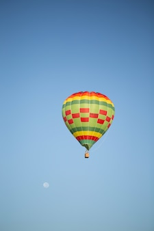 Beautiful vertical picture of hot air balloon over the clean blue sky
