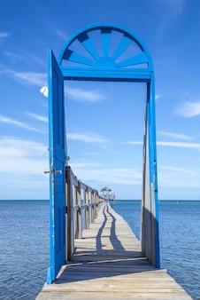 로아탄 섬의 낮에 나무 다리에 있는 파란 문의 아름다운 수직 사진