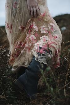 淡いピンクのガウンと黒のブーツの女性の美しい縦の写真