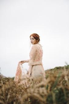 분홍색 가운에 순수한 흰색 피부를 가진 생강 여성의 아름다운 세로 사진