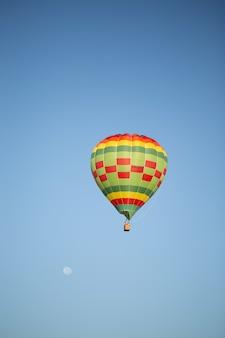 깨끗한 푸른 하늘 위로 열기구의 아름다운 세로 그림