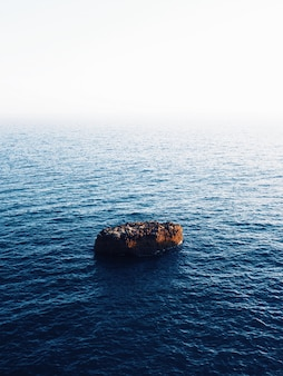 Beautiful vertical shot of a brown rock in the middle of the sea with amazing water textures