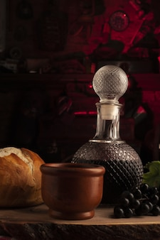 Beautiful vertical shot of a glass decanter with bread and pottery mug on the side