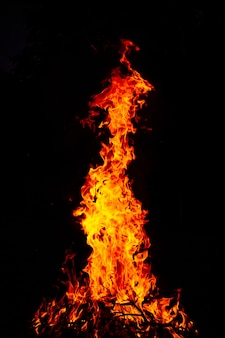 Bella ripresa verticale di un grande fuoco ardente di notte