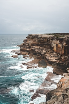 Beautiful vertical shot of a large cliff next to blue water on a gloomy day