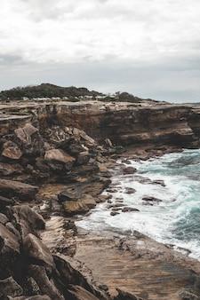暗い日に青い水の横にある大きな崖の美しい垂直ショット-壁紙に最適