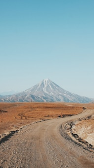 Красивая вертикальная съемка узкой пышной и грязной дороги с высокой горы