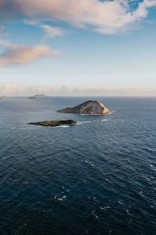 昼間の曇り空の下で海の小さな丘の美しい垂直ショット