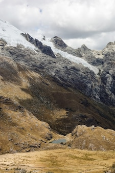 Bellissimo scatto verticale delle valli e della neve sui monti huascaran in perù