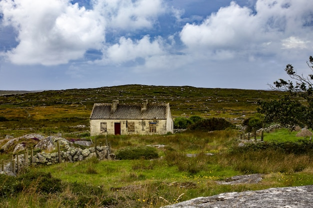 Bella vista di un cottage abbandonato nella contea di mayo su un campo erboso sotto il cielo nuvoloso