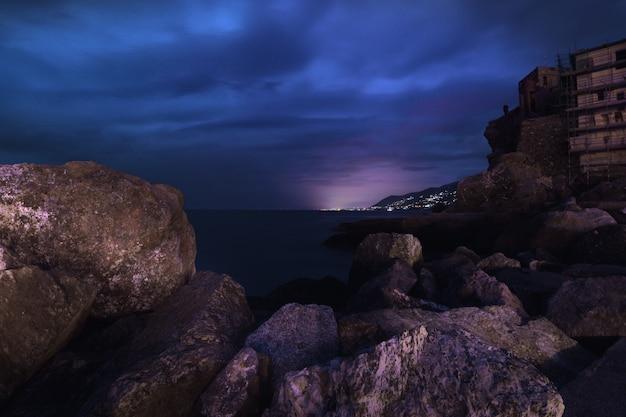 海の岩とジェノアの街の美しい景色