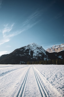 Beautiful view of the blue sky with mountains and a snowy road with tire tracks  during winter