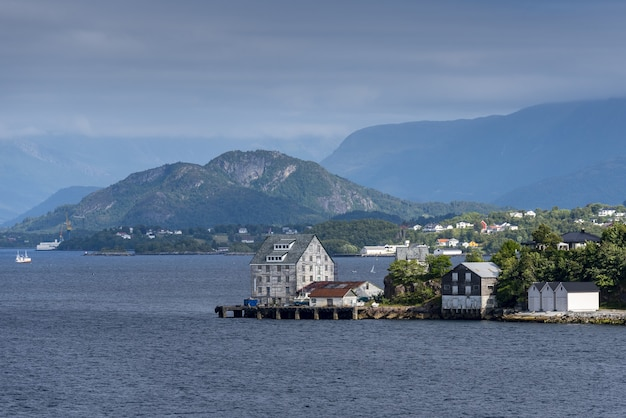 Beautiful view of buildings on the shore near alesund, norway with high mountains