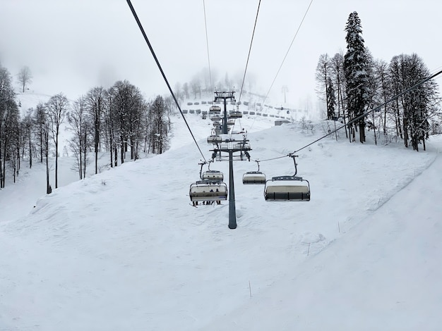 A beautiful view to the cabs of the ski lift through the fog in the mountains