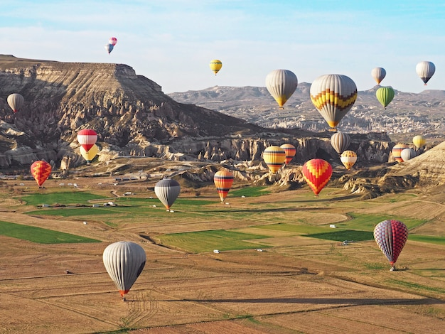 Beautiful view of colorful hot air balloons flying over landscape in cappadocia, turkey.