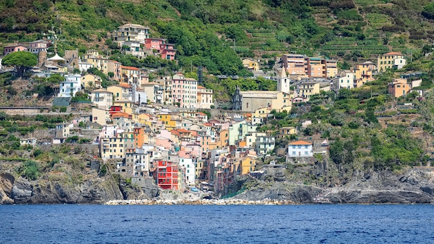 Beautiful view of the colorful houses of riomaggiore on the sunny day from sea. italy