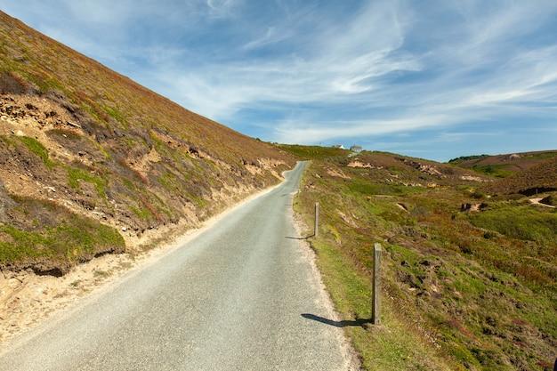 Bella vista della strada di campagna in cornovaglia, regno unito sotto il cielo blu