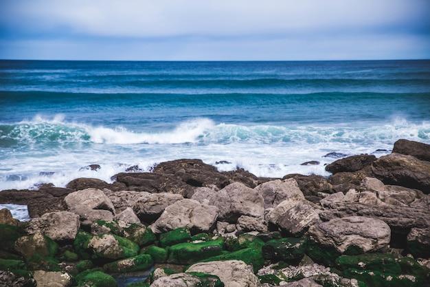 崖の近くの海岸の美しい景色の泡の波
