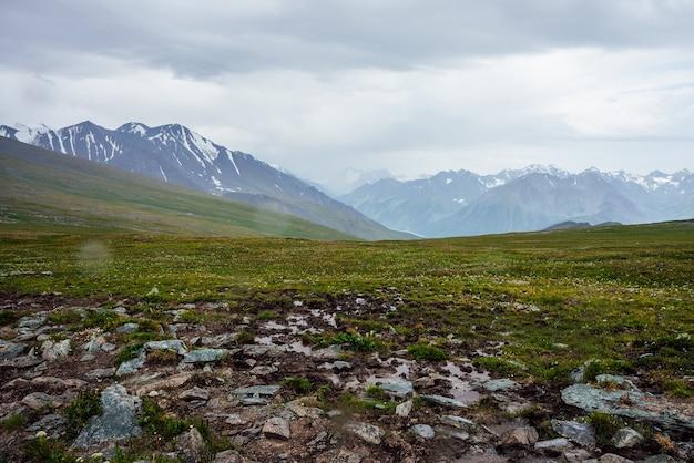 Прекрасный вид с перевала на большие заснеженные горы под пасмурным серым небом.