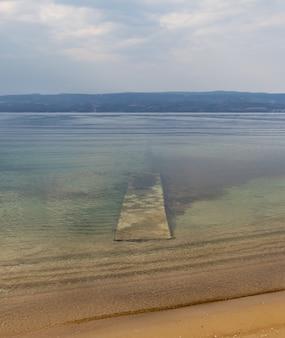 Прекрасный вид с пляжа на чистое озеро с горами