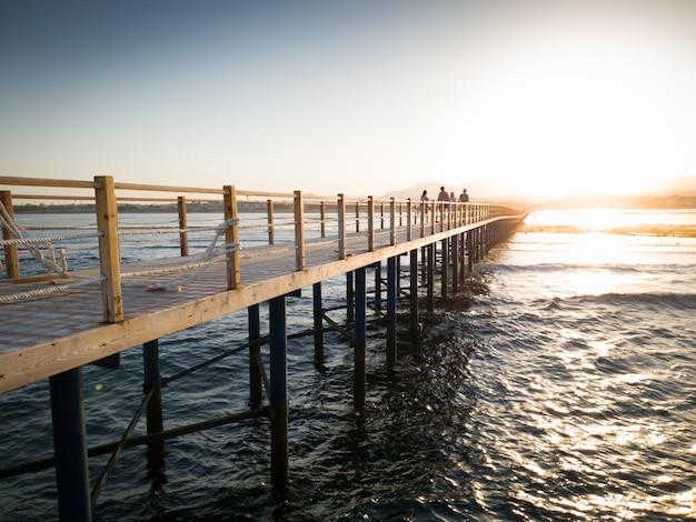 Прекрасный вид с деревянного пирса или моста на спокойные морские волны океана и закат над горами