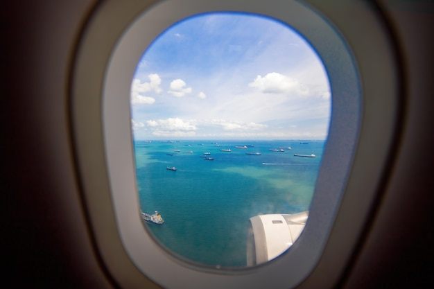 Beautiful view from the window of plane sea and cargo ships carefree view porthole landing airplane