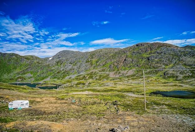 Bella vista sulle montagne coperte d'erba e sui campi sotto il cielo blu chiaro in svezia