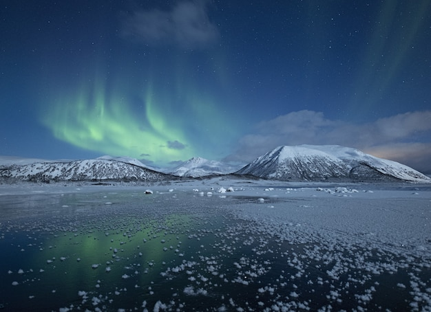 Beautiful view of the half froze lake surrounded by snow covered hills under the northern lights