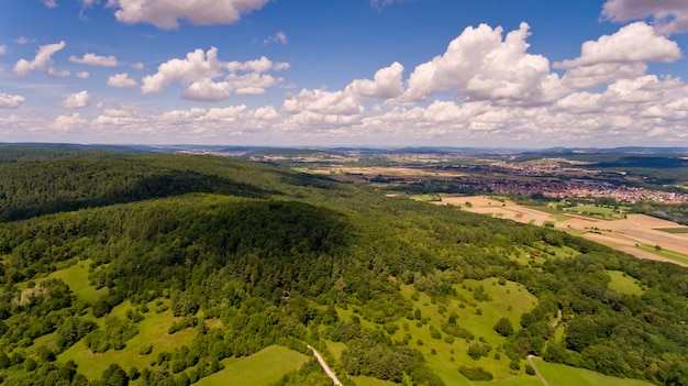 Beautiful view of a hill with a green forest and blue sky with white clouds. aerial view.