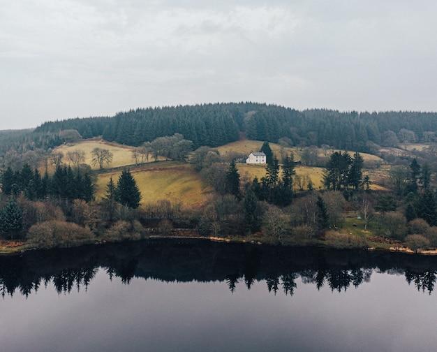 Bella vista di una casa vicino a un lago circondato da alberi in un bosco