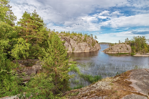 Beautiful view of lake and small stone islands covered trees and grass