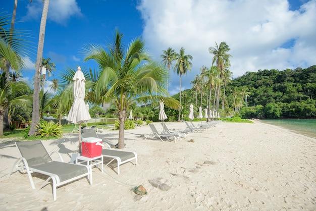 熱帯のビーチ、エメラルド色の海、青い空を背景に白い砂浜のラウンジチェアの美しい景色の風景